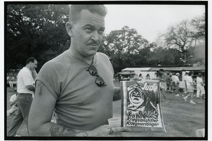 "Man holding Nazi-era sign at rally for David Duke. Translation is ""The Jew: War Agitator. War Perpetuater."" New Orleans, LA, July 4, 1991"