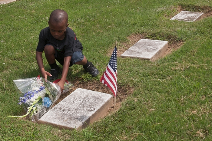Young boy lays wreath on the grave of a Yorktown soldier who served with the United States Colored Troops during the Civil War, Yorktown, VA, July 23, 2013