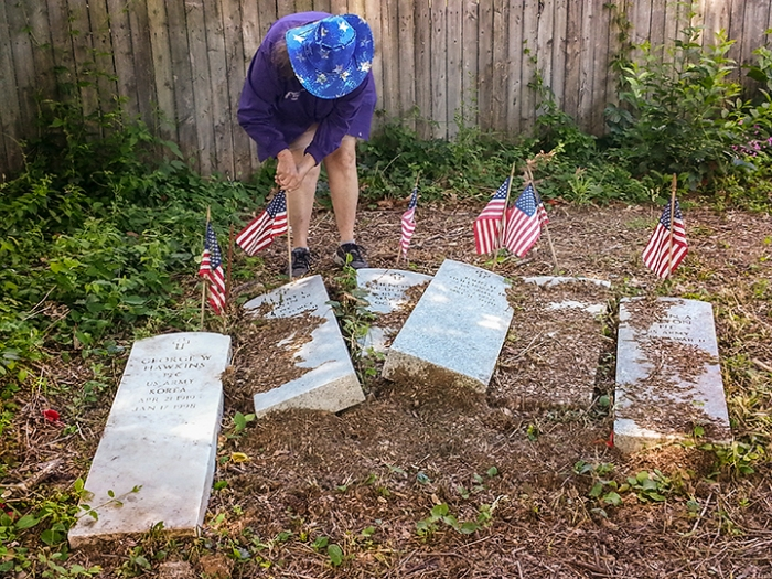 Marquita Latta plants flags at upended headstones of black servicement, Oakland Cemetery, Hampton, VA, May 24, 2014