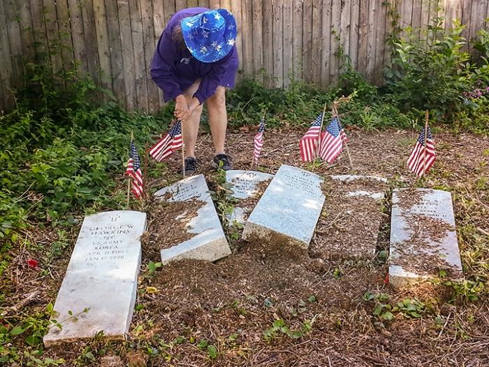 Marquita Latta plants flags at upended headstones of black servicement, Oakland Cemetery, Hampton, VA, May 24, 2014