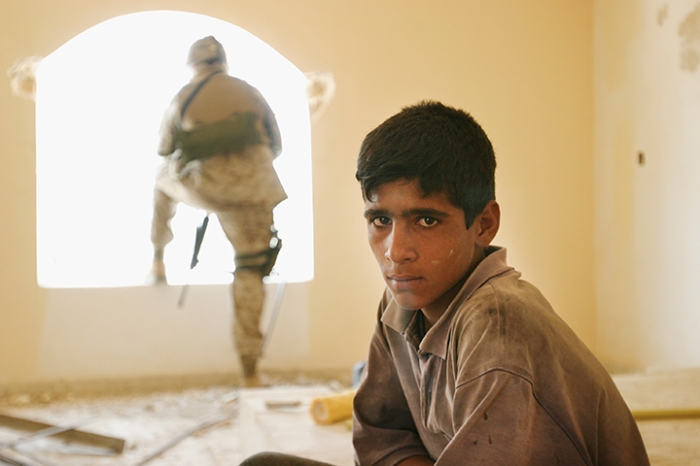 Boy on construction team building birthing center funded and then defunded  by U.S. Army. Marines promised to resume support — if local leaders cooperated with them. Jurf-al-Sakhar, Iraq, August 8, 2004
