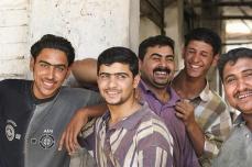 Iraqi men on sidewalk laugh as US Marine patrol from 1/2 passes, Iskandariyah, Iraq, August 3, 2004